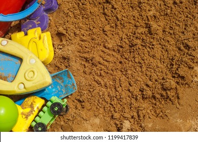 Bright colored children's toys in the sandbox. Close-up. Background. Copy space