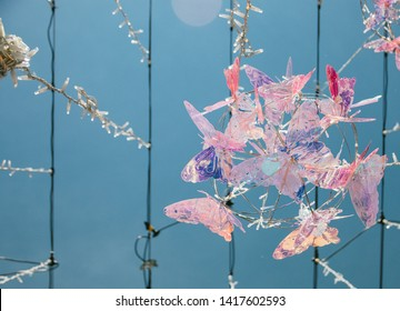 bright colored decorative butterflies and garland hanging on special wires decorating the street of the city, at night burning illumination