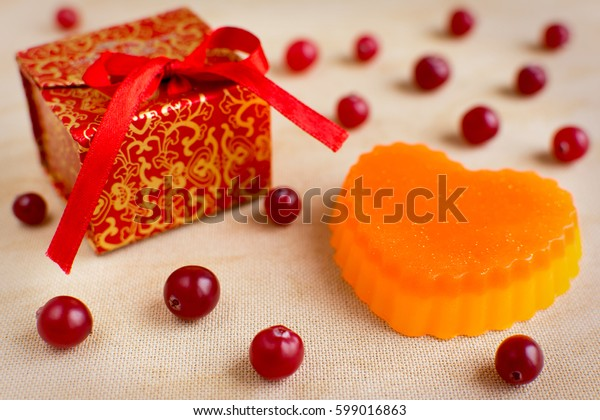 Bright colored exclusive handmade soap in the shape of heart. Cranberries and red gift box on the background.
