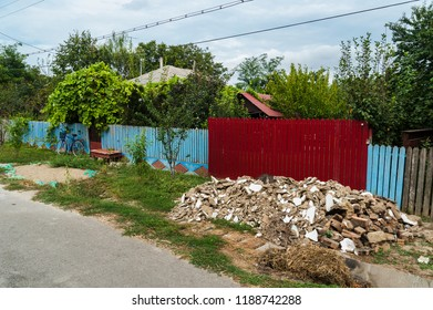 Bright colored fences/Romanian village street with colored wooden fences, a pile of debris and a bike leaning on a blue fence.