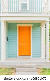Bright colored front door of remodeled urban home, tangerine orange and light turquoise baby blue