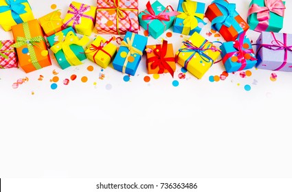 Bright Colored gift boxes with bright ribbons and confetti. White background. Gifts for Christmas or birthday.