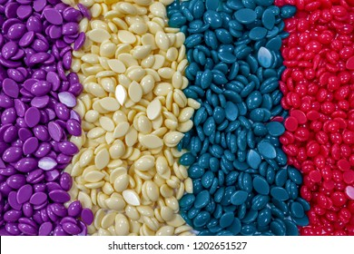Bright colored granules. Abstract beautiful background. Granules for hair removal. Vivid colorful yellow, purple, green, red Wallpaper