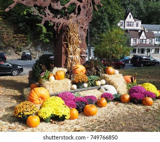 bright colored mum flowers, orange pumpkins and hay bales by a tree.  The ground has fallen leaves.