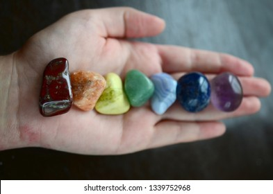 Bright colored rainbow crystal layout. Healing crystal of all colors, variety of stones. Colorful healing crystals, on wood background. Hand holding crystals, healing reiki chakra gemstones.