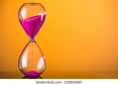 Bright colored time with hourglass on a yellow background.
