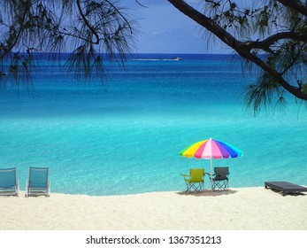 A bright colored umbrella and chairs is the perfect place to relax on a beach in Bimini, Bahamas to look out over the turquoise an blue ocean while watching boats speed by on a beautiful sunny day.