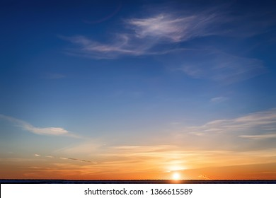 Bright colored winter sunset. Yellow clouds on the horizon and blue sky