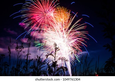 Bright and colorful 4th of July fireworks in a dark night sky over the water in Priest River Idaho