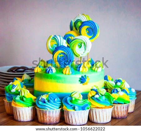 Bright Colorful Cake With Cupcakes Standing Around