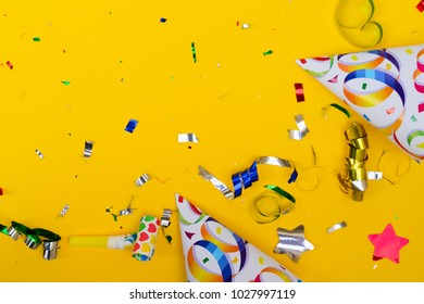 Bright colorful carnival or party frame of confetti on yellow background frame. Flat lay style, birthday or party greeting card with copy space.