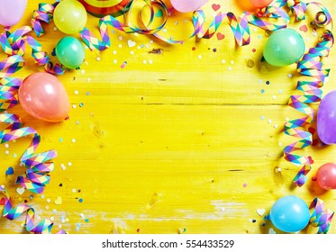Bright colorful carnival or party frame of balloons, streamers and confetti on a rustic yellow wood table with central copy space for your greeting , invitation or advertising