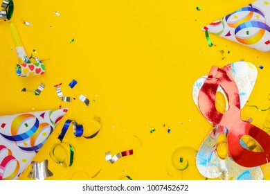 Bright colorful carnival or party scene of confetti and masks on yellow table. Flat lay style, birthday or party greeting card with copy space.