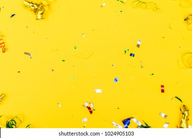Bright colorful carnival or party scene of metalic confetti on yellow background. Flat lay style, birthday or party greeting card background