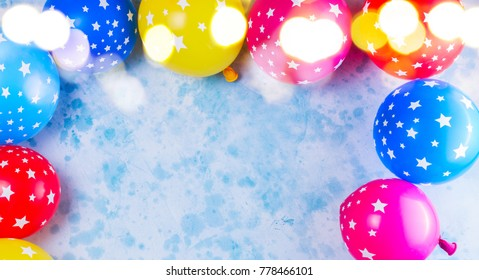 Bright colorful carnival or party scene frame of balloonson blue table. Flat lay style, birthday or party greeting card with copy space.