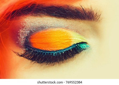 bright colorful female closed eye with professional fashionable glamour makeup orange blue color with long eyelashes and eyebrow, closeup