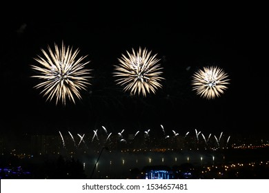 Bright colorful fireworks against dark night sky reflected in river water