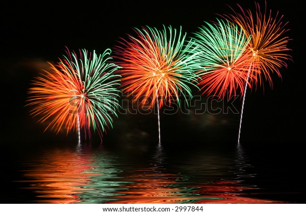 Bright and colorful fireworks display with reflection on water.