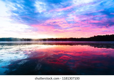 Bright colorful foggy sunset on the lake with clouds and reflections in Finland. Nature amazing sunrise background.