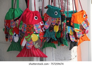 Bright colorful hand made cotton fish for souvenirs hanging on a wall in the tourist town of Fira on Santorini in Greece.