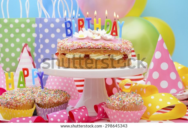 Bright colorful Happy Birthday Party Table with balloons, streamers, party favor gift bags and birthday cake with lit candles.