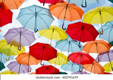 Bright colorful hundreds of umbrellas floating above the street