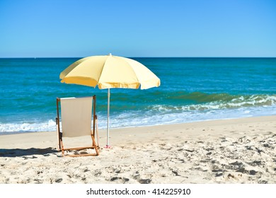 Bright colorful image of yellow umbrella and white wooden chair on Atlantic sandy beach blue sky copy space background