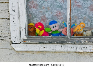 Bright and colorful old toy sitting on windowsill behind glass of abandoned house.