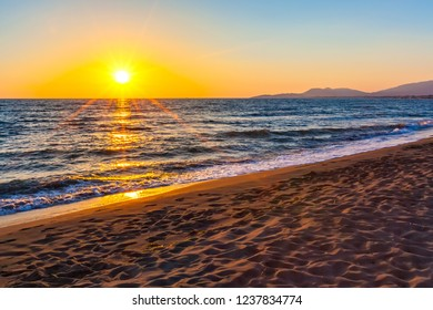 A bright colorful orange sunset on the Adriatic Sea, the rays of the sun illuminate the waves in gold and scatter the soft light along the coast. Beach on Ada Bojana, Ulcinj, Montenegro.