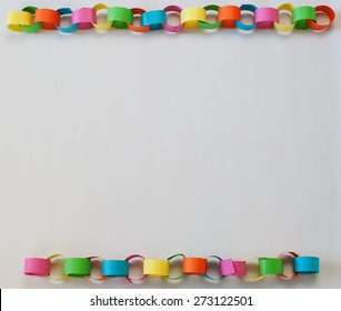 A bright and colorful paper chain border on a white background
