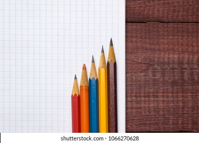 Bright colorful pencils next to a blank sheet of paper. School supplies stationery on a wooden texture table. Trendy minimalism. Concept back to school. Top view