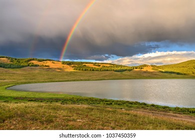 Bright colorful rainbow over the mountains, lake and forest after the rain against the blue sky with clouds in summer