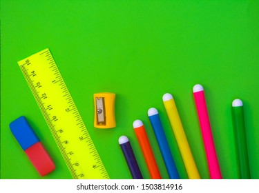 Bright and colorful set of school and office supplies on  green background. Horizontal top view. Free copy space. Can be used as bakground