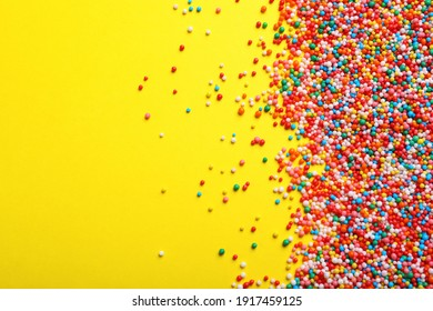 Bright colorful sprinkles on yellow background, flat lay with space for text. Confectionery decor