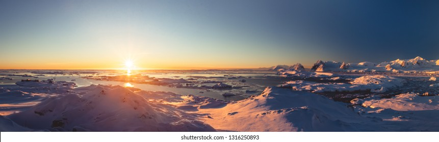 Bright colorful sunset panorama view in Antarctica Ocean. Orange sun lights over the snow covered polar surface. Picturesque winter landscape. The beauty of the wild untouched Antarctic nature.