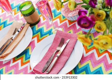 Bright colorful table setting with multi-colored chevron pattern tablecloth