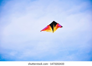 Bright and colorful triangle kite against blue sky