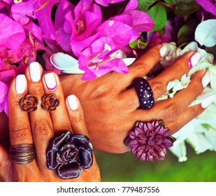 bright colorfull shot of african tanned hands with manicure among pink flowers wearing jewellery