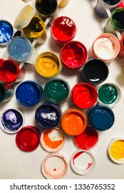 Bright colors in banks. Background of colored paints. Gouache. Paint on white background. Yellow, green, red, orange, blue paint. Gouache for painting. Children's creativity. Hobby drawing