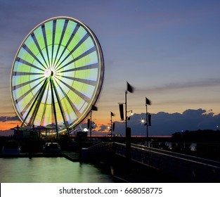 Bright colors illuminating the ferris wheel in motion at National Harbor on the Potomac