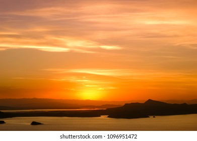 Bright colors in the sky and sunset reflection in the waters of Lake Titicaca, Puno, Peru and Amantany Island.