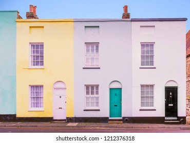 Bright colourful symmetrical row, terrace houses each with two sash windows and lunette arch above the doors which also have knockers.