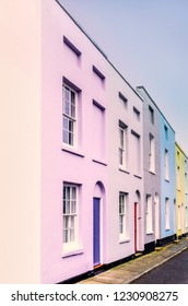 Bright colourful symmetrical row, terrace houses, lilac, blue, yellow each with two sash windows and lunette arch above the doors