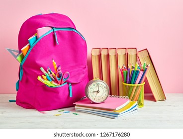 Bright composition from a school stationery on a pink background. School and office supplies frame