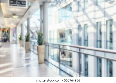 Bright corridor with perspective lines and columns with fresh flowers in pots on the background of the windows in the interior of a modern building. Blurry
