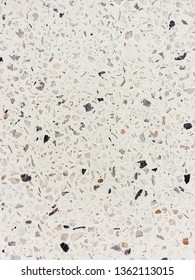 Bright crisp unpolished terrazzo texture background with dark and bright small stones and white cenent filling.