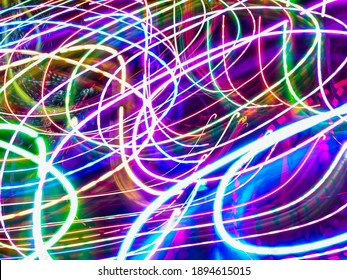 Bright crisscrossing light trails in an ornamental garden with holiday illumination at night. Long exposure with motion blur. Light painting.