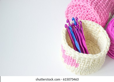 Bright crochet boxes and crochet hooks with numbers. Pink and white crochet textile tutorial pattern. Thick ribbon cotton yarn