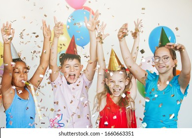 Bright, cute children celebrate a birthday. Multinational party, balloons, confetti, caps, smiles, teenagers are happy raising their hands up.