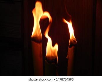 Helle tanzende Flammen von drei Gartenfackeln bei Nacht, Kopienraum